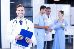 Doctor holding medical report and smiling at camera Royalty Free Stock Photography