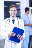 Doctor holding medical report and smiling at camera. While his colleagues discussing in background Stock Image