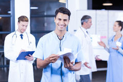 Doctor holding medical report and smiling at camera. While his colleagues discussing in background Stock Photography