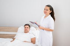 Doctor holding medical reports of patient Royalty Free Stock Image