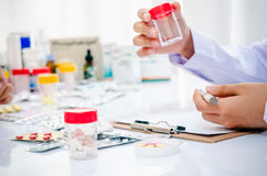 Doctor holding a medicine container Stock Images