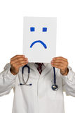 Doctor holding negative smiley face before Royalty Free Stock Image