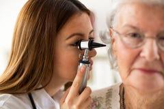 Doctor holding otoscope and examining ear of senior woman Stock Photo