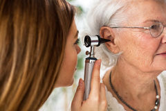 Doctor holding otoscope and examining ear of senior woman Stock Photos