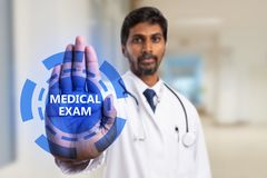 Doctor holding palm on screen with medical exam button. Indian male doctor holding palm on transparent screen with medical exam blue button as futuristic concept stock photo