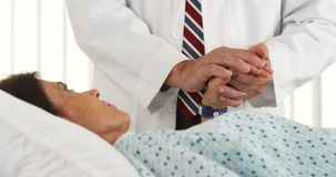 Doctor holding patient's hand and comforting her Stock Photos
