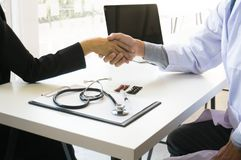 Doctor holding patient& x27;s hand, and reassuring his male patient h royalty free stock image