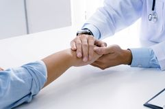 Doctor holding patient& x27;s hand, and reassuring his male patient h stock photography