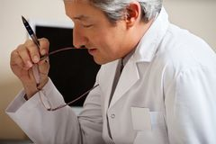 Doctor Holding Pen And Glasses Royalty Free Stock Image
