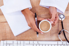 Doctor holding pen and hot beverage Stock Photo