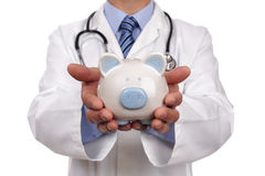 Doctor holding piggy bank. Concept for healthcare insurance fees and savings for medical expenses Stock Image