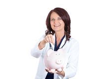 Doctor holding piggy bank. Healthcare reform concept. Doctor holding piggy bank about to drop a coin in it. Medical insurance medicare reimbursement. Happy Stock Image