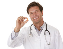 Doctor holding a pill. Caucasian doctor is holding a pill on white isolated background Royalty Free Stock Photos