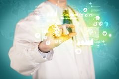 Doctor holding a pill between fingers. A doctor in white coat with a stethoscope on one shoulder holding a pill with green glowing graphs, lines, numbers, charts Stock Photos