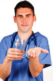 Doctor holding a pill and a glass of water Royalty Free Stock Photo