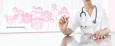 Doctor holding pill medicine with pink icons. Health care concept. Doctor holding pill medicine with pink icons. Health care and medical woman concept Stock Photo