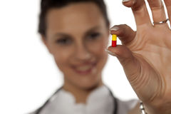 Doctor holding a pill. Young woman doctor holding a capsule pill Stock Images