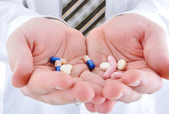 Doctor holding pills Stock Photography