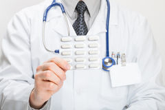Doctor holding pills in hand Stock Photo