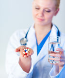 Doctor holding pills to camera Stock Photography