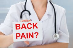 Doctor holding placard with back pain text Royalty Free Stock Image