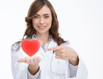 Doctor holding and pointing at a red heart Royalty Free Stock Images