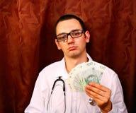 Doctor holding polish money Royalty Free Stock Photos