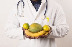 Doctor holding and presenting fruits in hands stock photos