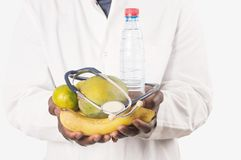 Doctor holding and presenting fruits in hands stock photo