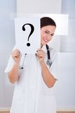 Doctor holding question mark sign in hospital Stock Image