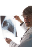 Doctor holding x-ray. A smiling male doctor in a white coat holds up an x-ray film Stock Image