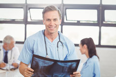Doctor holding a x-ray report in conference room. Portrait of happy doctor holding a x-ray report in conference room and colleagues discussing in background Royalty Free Stock Image