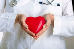 Doctor holding red heart. Female doctor holding red heart Royalty Free Stock Image