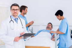Doctor holding reports with patient and surgeon in background royalty free stock photo