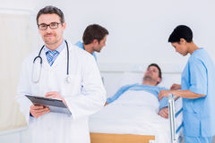 Doctor holding reports with patient and surgeon in background Royalty Free Stock Images