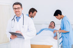 Doctor holding reports with patient and surgeon in background Stock Photography
