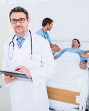 Doctor holding reports with patient and surgeon in background Stock Photos