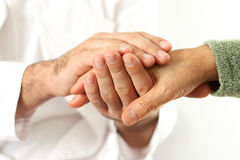 Doctor holding senior's hands Royalty Free Stock Photography