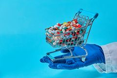 Doctor Holding Shopping Cart With Full Of Pills. stock photos