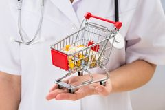 Doctor holding shopping cart with pills Stock Photography