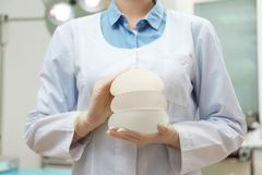 Doctor holding silicone implants for breast augmentation in clinic. Cosmetic surgery. Doctor holding silicone implants for breast augmentation in clinic, closeup stock images