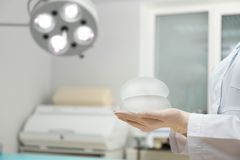 Doctor holding silicone implants for breast augmentation in clinic, space for text. Cosmetic surgery stock photography