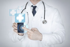 Doctor holding smartphone with medical app Stock Image