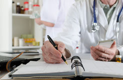 Doctor holding a smartphone and taking notes Stock Images