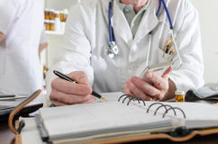 Doctor holding a smartphone and taking notes Stock Photos