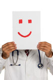 Doctor holding smiley face before Stock Photos