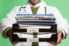 Doctor holding a stack of paperwork Stock Photography