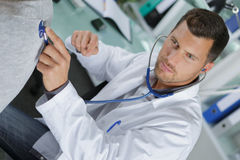 Doctor holding stethoscope in hand and doing auscultation. Doctor holding stethoscope in his hand and doing auscultation stock photos