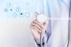 Doctor holding stethoscope in hand with modern medical technology background royalty free stock photos