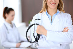 Doctor holding a stethoscope in his hand , against the background of another doctor Royalty Free Stock Photos